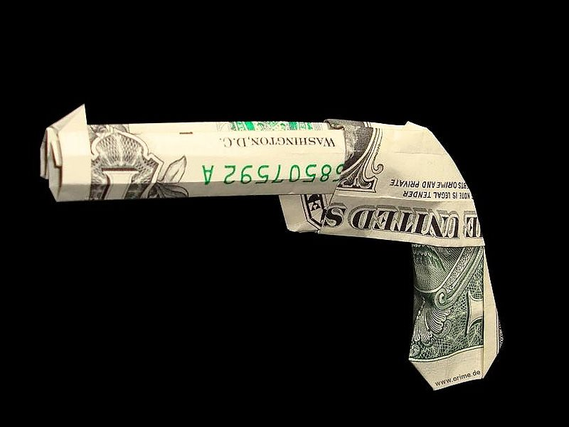 Orgami with a dollar bill in the shape of a gun.
