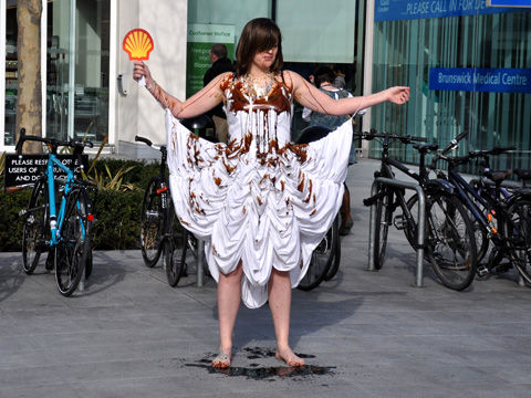 A Climate Rush member stands outside of Waitrose covered in 'oil'