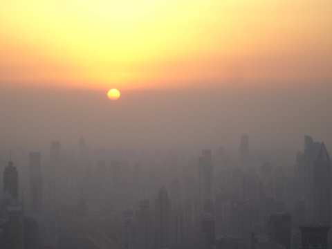 Shanghai at sunset seen from the Jin Mao tower observation deck. The sun has not yet dropped below the horizon; it has simply reached the smog line. Wikimedia commons / Suicup.