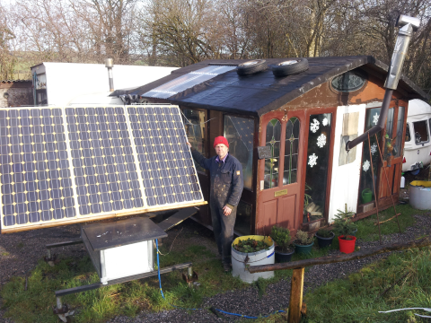 Andy enjoys the sunshine outside 'The Shack' - while solar panels charge up the batteries. Photo: Solar Events.