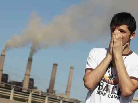 A clean energy campaigner shields his face in front of the Kosovo B coal power station, which is doing much to destroy the small nation's health. Photo: Sierra Club.