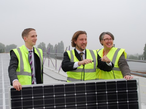 Luke Marion, installer Chris Jardine and Barbara Hammond connect the 140kW scheme's last panel, completing Oxford's biggest solar installation.