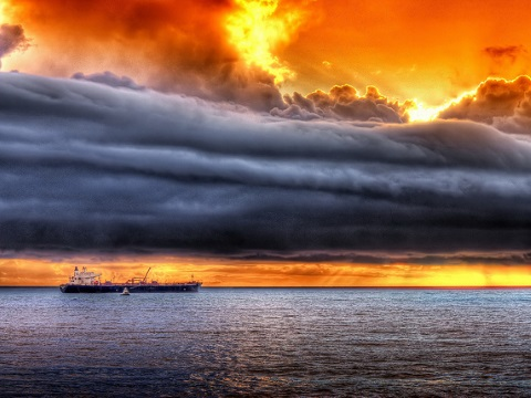 Dark clouds gather over a sunset industry - represented by a Chevron oil tanker. Photo: Jamie Grant via Flickr.