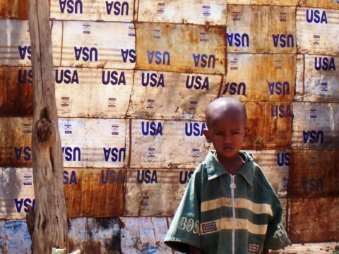 A child leans against a wall made of USAID food aid containers in the flood-destroyed area of Bahere Tsege in Dire Dawa, Ethiopia. Photo: Liz Lucas / Oxfam America.