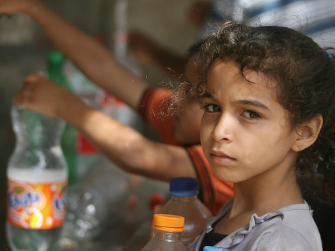 Children in Rafah collect water from one of the working public taps, 13th July 2014. But with the bombing of water infrastructure and Gaza's only power station, it's unlikely to be working today. Photo: Oxfam International via Flickr.