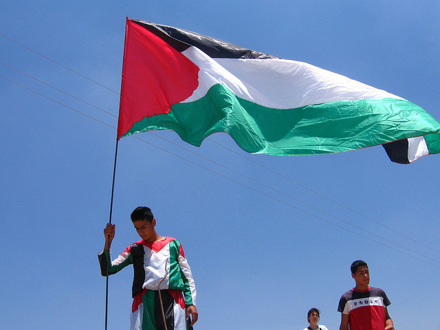 Palestinian demands for freedom and justice will never be relinquished. The Palestinian flag flying at a demonstration at Bil'in on the West Bank. Photo: Adam Walker Cleaveland.