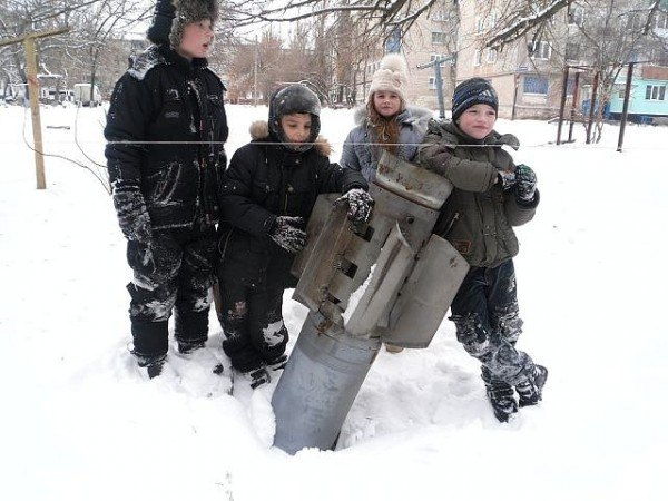 Children gather around an unexploded shell fired by Kiev forces into a residential area of Eastern Ukraine. Photo: Colonel Cassad (cassad-eng.livejournal.com).