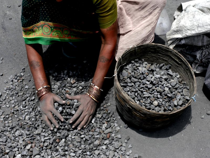 Path to riches? A woman rummages through mining overburden in search of left-over coal to sell at Jugsalai, Jharkhand. India. Photo: Akshay Mahajan via Flickr (CC BY-NC-SA).