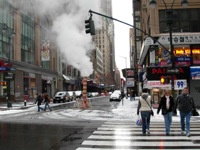 The New York Steam Company commenced its piped heat distribution in the city in 1882. Steam venting from the street at 33rd and 5th Avenue, December 2007. Photo: Paul Churcher via Flickr (CC BY).
