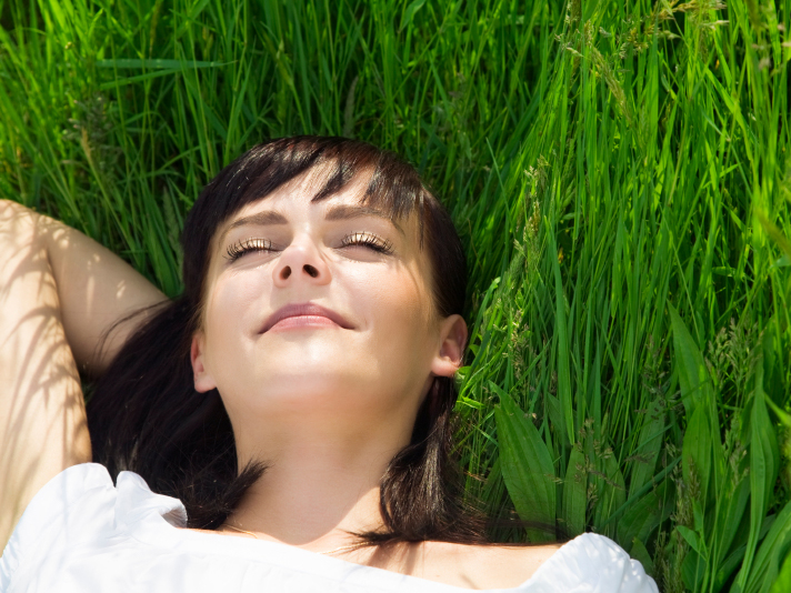 a woman's head rests amongst green grass