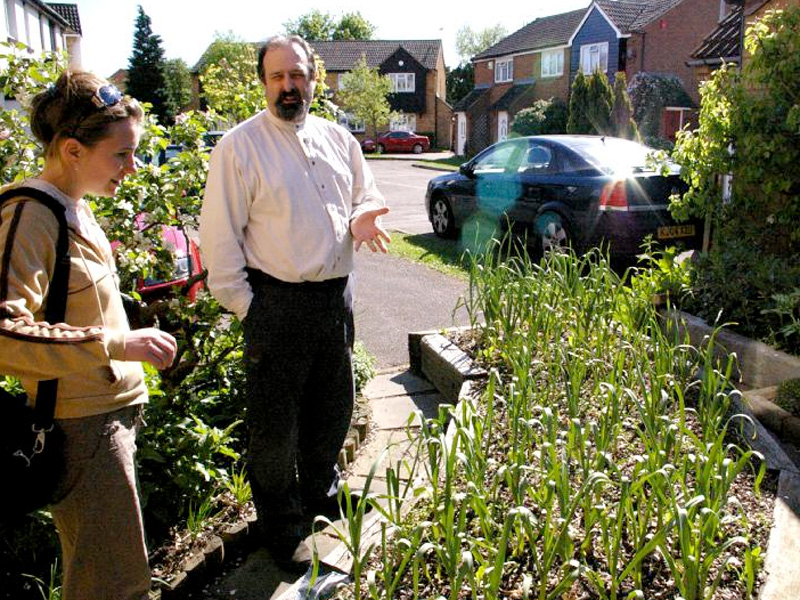 Mike Guerra explains his permaculture garden to Louise Parry