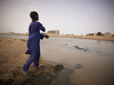 A boy skims a stone on the water covering his former school