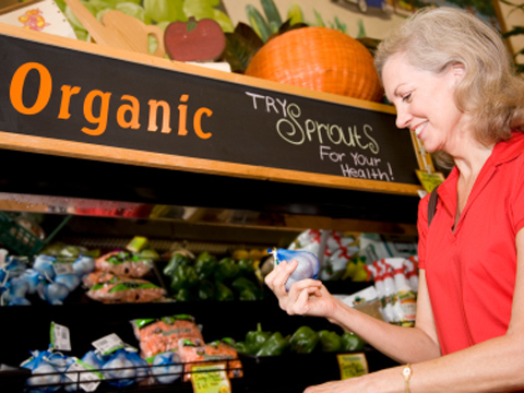 Older lady shopping for garlic in organic aisle