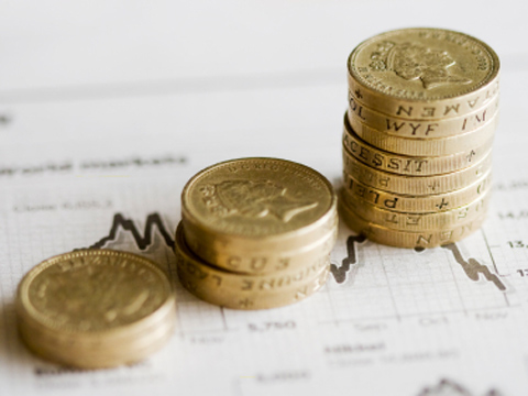 stacks of pound coins on a stock chart