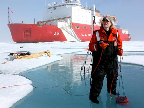 ICESCAPE scientist Karen Frey taking optical measurements in a melt pond, with US Coast Guard Cutter Healy. Photo: NASA's Goddard Space Flight Center / Kathryn Hansen.