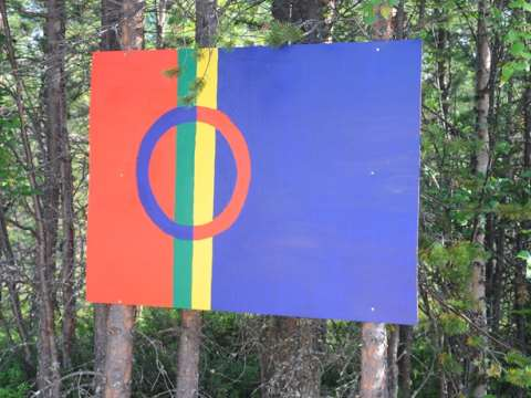 The colours of the Sami flag painted on a board at the site of the mine. Photo: Alec Forss.