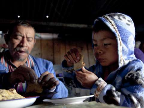 A former undocumented worker in the USA, Marvin Garcia Salas shares food with his son, Jesus, at home in Chiapas, Mexico. Photo: Bread for the World via Flickr.