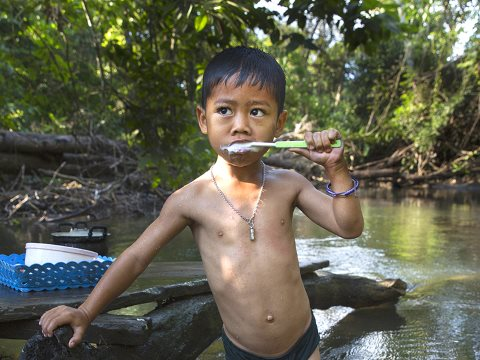A child brushes his teeth in lead-contaminated water in Klity Creek, Thailand. Photo: Human Rights Watch.