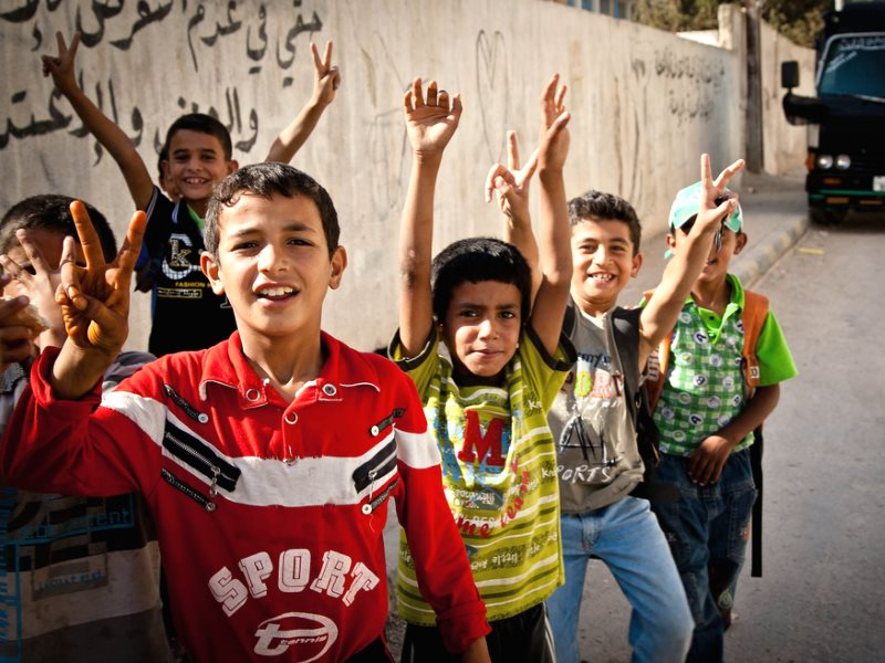 Love and peace! Boys in the Jerash Palestinian refugee camp in Jordan gather to raise their hands in peace signs. Photo: Omar Chatriwala via Flickr (CC BY-NC-ND).