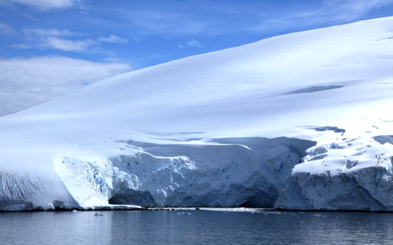 Ice may be breaking off the Antarctic's sea shores, but in its vast centre, ice mass is growing three times faster. Photo: Glacier in Penola Strait, Antarctica, by Liam Quinn (CC BY-SA).