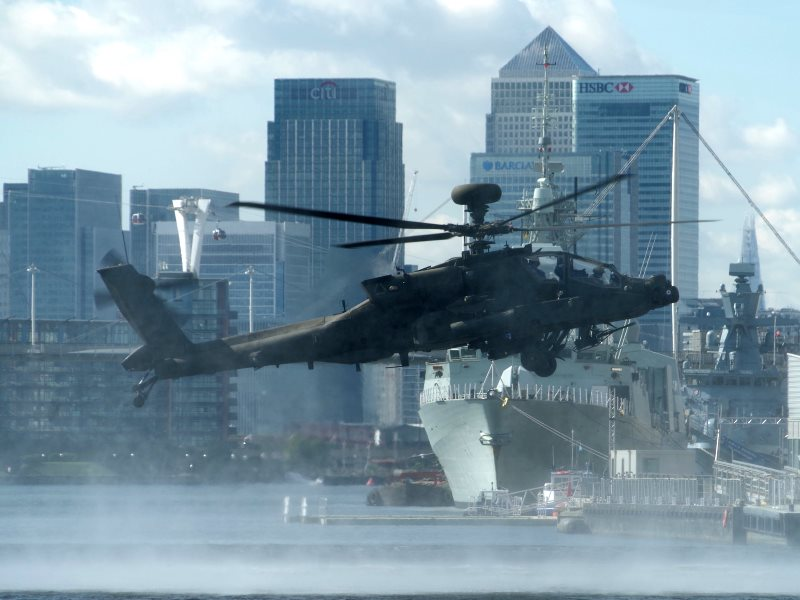 Finance and terror, war and profit: never far apart. A US army helicopter hovers over Royal Victoria Dock, away from the DESI 2015 arms fair at the ExCeL Centre, 19th September 2015. Photo: Matt Buck via Flickr (CC BY-SA).