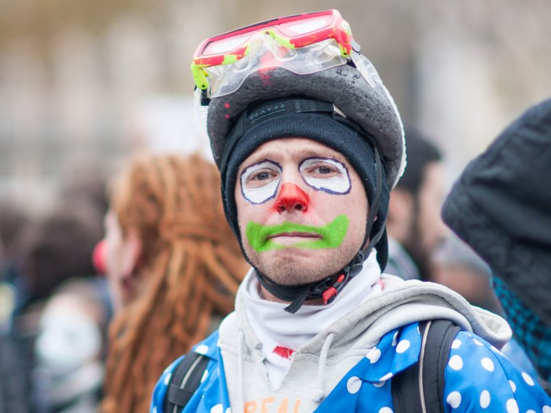 The real clowns are the ones inside the COP21 conference centre, deliberately obstructing and slowing down negotiations. A demonstrator in Paris on 29th November. Photo: Duc via Flickr (CC BY-NC-ND).