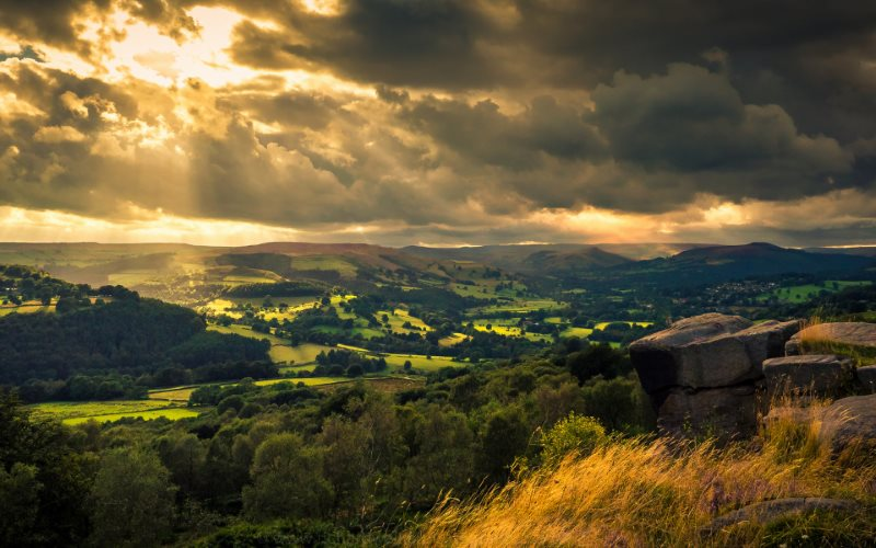 Sun breaking through the clouds over the Derwent Valley, Peak District, UK with the village of Hatersage in the distance. Photo: Richard Walker via Flickr (CC BY).