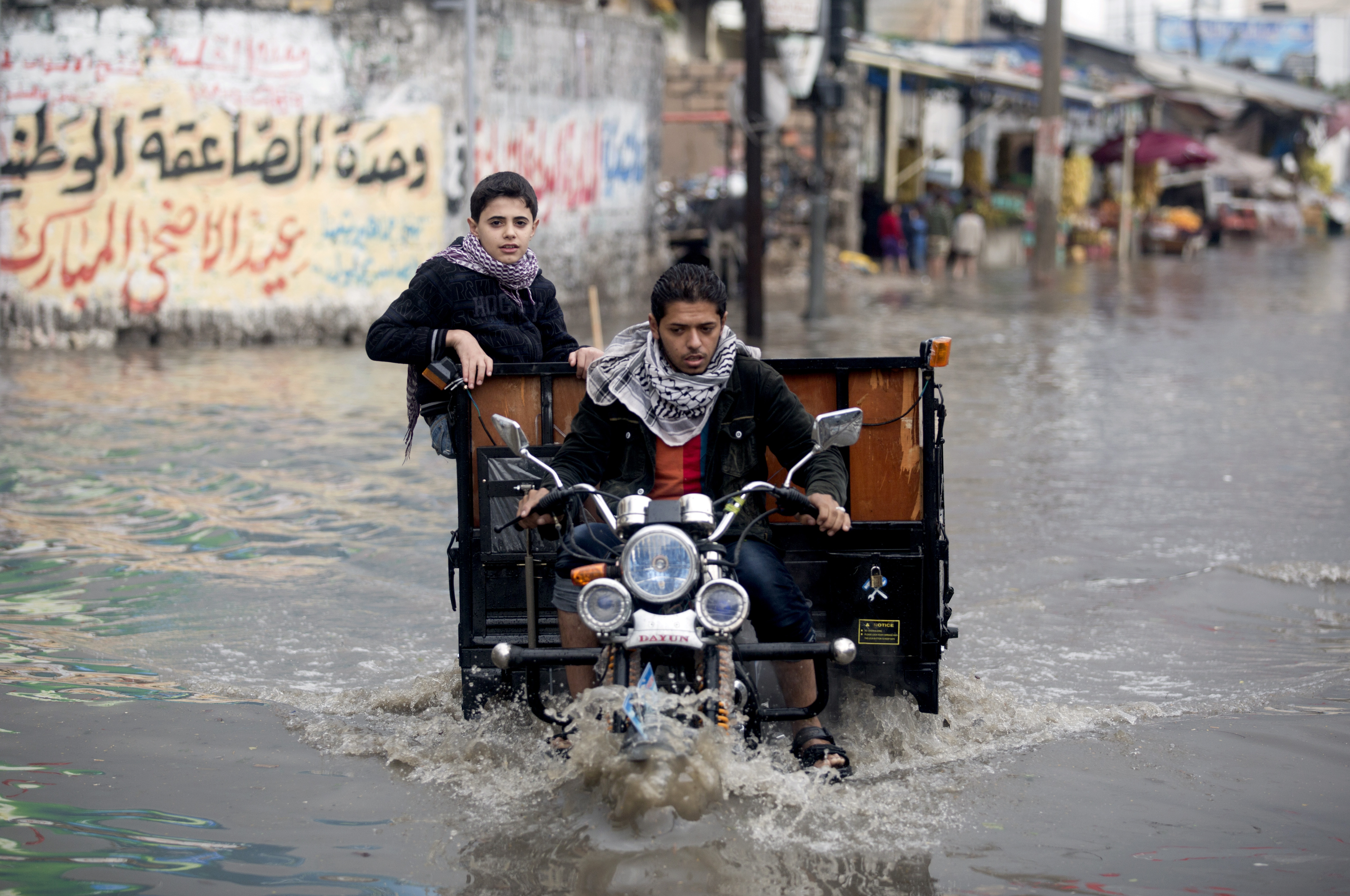 A Palestinian rides his trike through a flooded street following the heavy floods of 2013. Photo: AFP PHOTO/MOHAMMED ABED via Flickr/Globovisión (CC BY-NC 2.0)