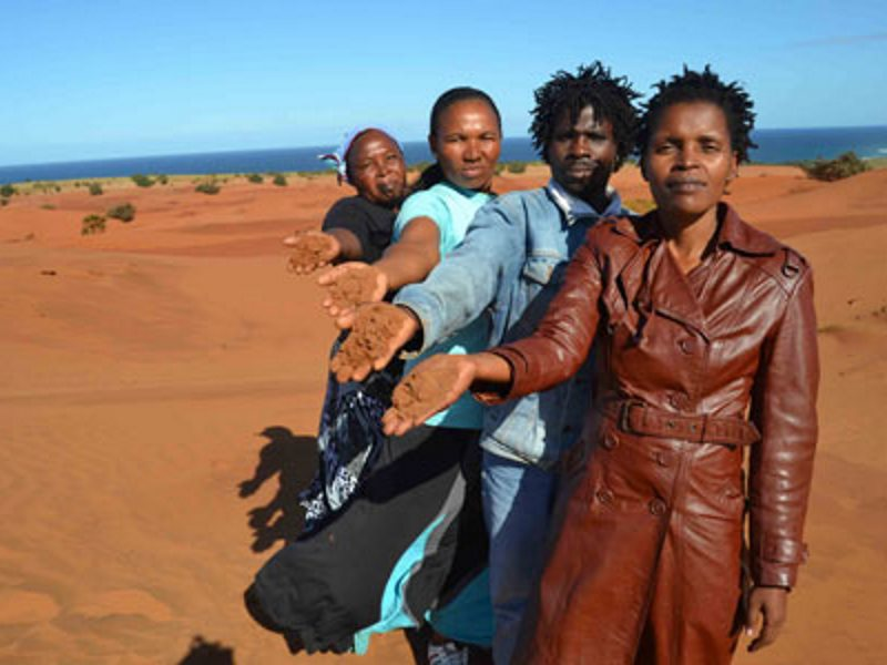 Nonhle Mbuthuma of Amadiba Crisis Committee shows the red sand at Kwanyana Beach near Xolobeni that is at the centre of the dispute. Photo: Loyiso Mpalantshane via Sustaining the Wild Coast.