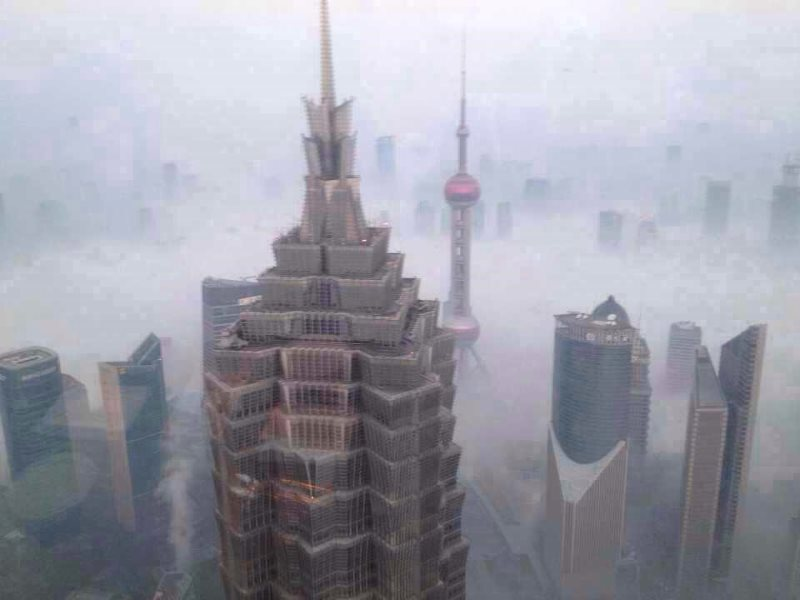 The costs of 'growth': Shanghai skyscrapers barely breaking the all-engulfing smog layer. Photo: erhard.renz via Flickr (CC BY).
