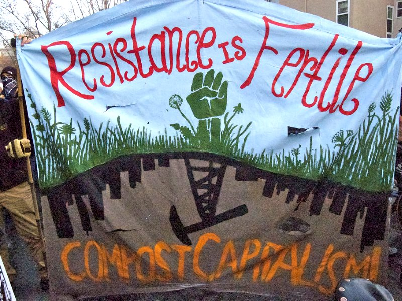'Resistance is Fertile - Compost Capitalism !' Banner at Occupy Oakland protest against GMOs, 10th December 2011. Photo: Lily Rhoads via Flickr (CC BY).
