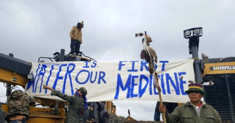 'Water is our first Medicine' - Water Protectors locked onto machinery, halting construction two days after the Dakota Access pipeline company bulldozed sacred burial sites. Photo: UnicornRiot.Ninja via Prachatai on Flickr (CC BY-NC-ND).