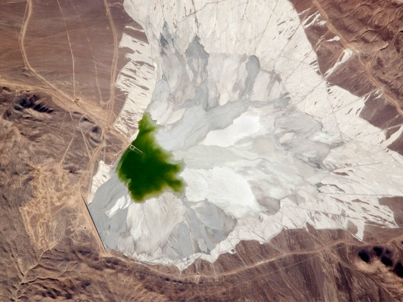 The Escondida copper-gold-silver mine, 170 kilometers (110 miles) southeast of Chile's port city of Antofagasta. This astronaut photograph features a large impoundment area (image center) containing light tan and gray waste spoil from of the Escondida m
