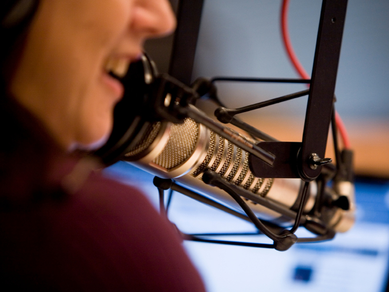 A woman's mouth near a radio stuido microphone