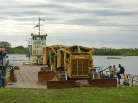 Bulldozer rolling off barge in Paraguay