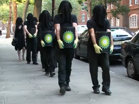 Protestors carry cans of 'oil' marked with BP logo