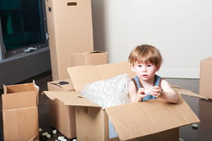 A child plays in an empty box.