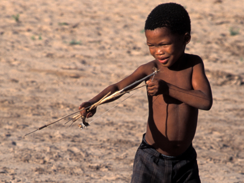Bushman boy with bow and arrow. Photo: Survival International.