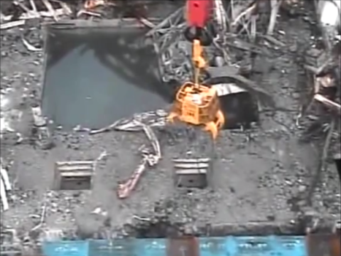 Clearing debris from around the spent fuel pond in Fukushima Building 3 in late 2013. Photo from Tepco video.