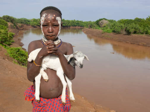A boy from the Lower Omo stands on the riverbank. Photo: © Survival