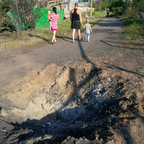 Family walking past a blast crater in Kandrashevka, where 9 civilians died during an aerial attack by alleged Ukranian forces on July 2, 2014. ©2014 Human Rights Watch.