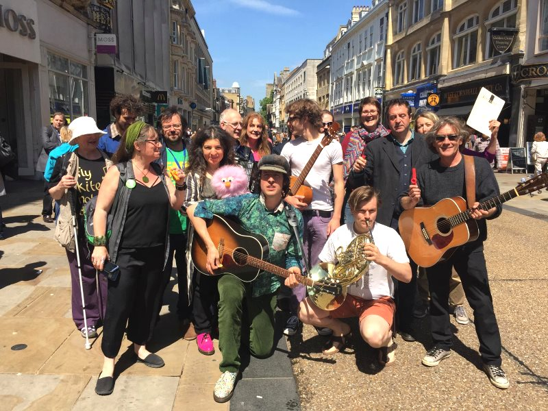 Jonny Walker (centre) and supporters of Keep Streets Live at a 'busk-in' on Oxford's Cornmarket, 27th May 2015, to protest the Labour Council's plans to criminalise busking and other 'non-compliant' behaviour. Photo: Keep Streets Live.