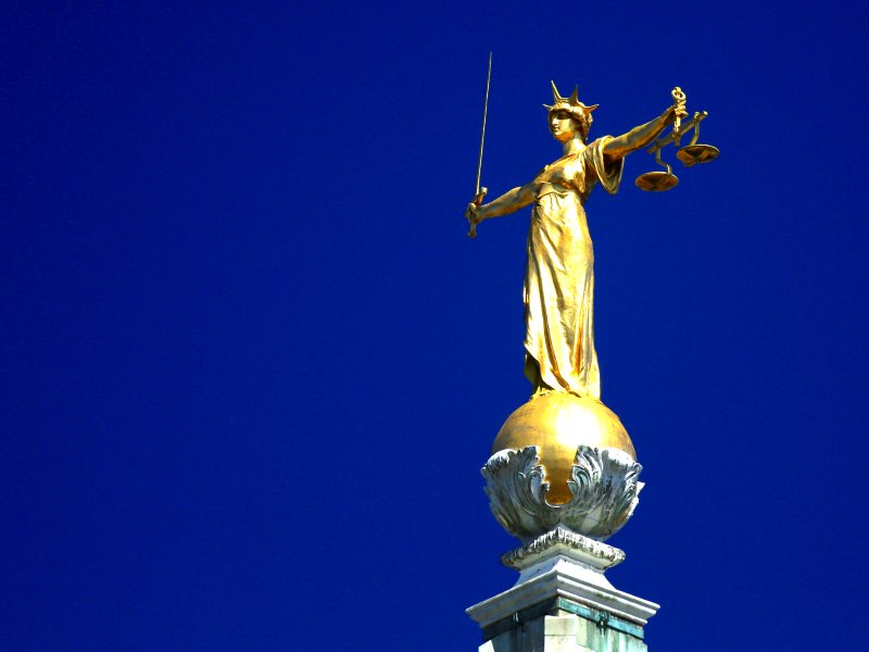 In case you didn't know, her scales are weighted. And government 'reforms' are only making them more so. The statue of Lady Justice atop England's Central Criminal Court, the Old Bailey. Photo: Ronnie Macdonald via Flickr (CC BY).