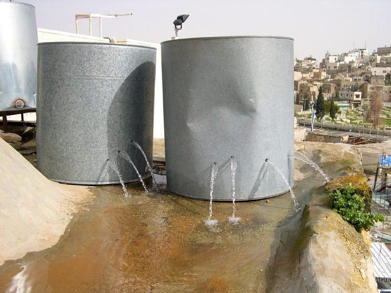 Holed Palestinian water tanks, destroyed by armed settlers in the old city of Hebron. Photo: ISM Palestine via Flickr (CC BY-SA).
