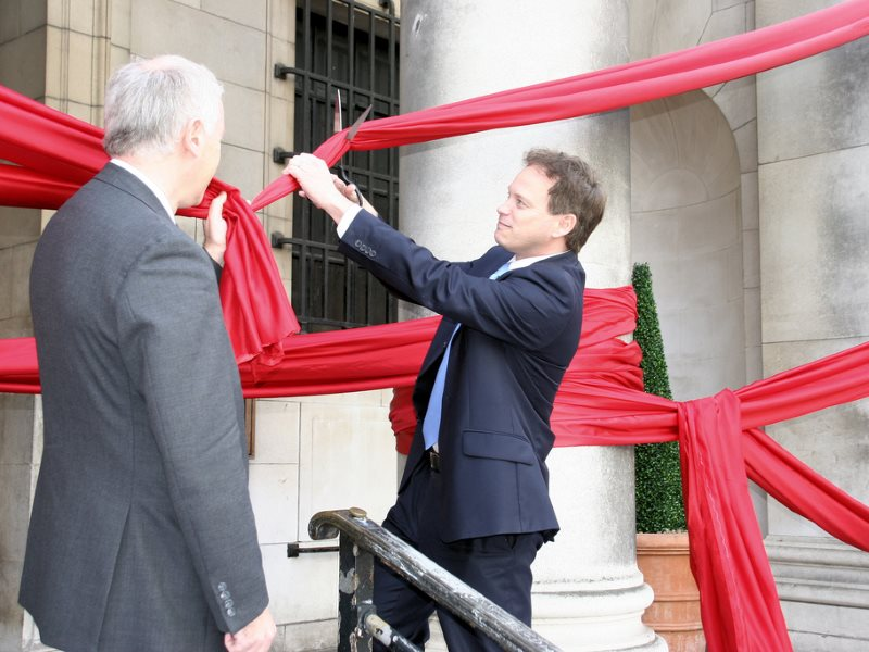 Grant Shapps MP cutting away at 'red tape' to demonstrate the government's commitment to corporate deregulation no matter what the cost to health, safety and environment. Photo: Department for Communities and Local Government via Flickr (CC BY-ND).