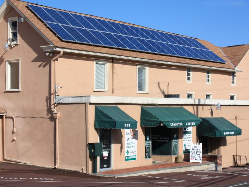 With 50 times more solar power on a 'net metering' basis than now (5% vs 0.1%), electricity costs in Pennsylvania would fall by $25 per customer. Business with solar panels in Harleysville, PA. Photo: Montgomery County Planning Commission via Flickr (CC B