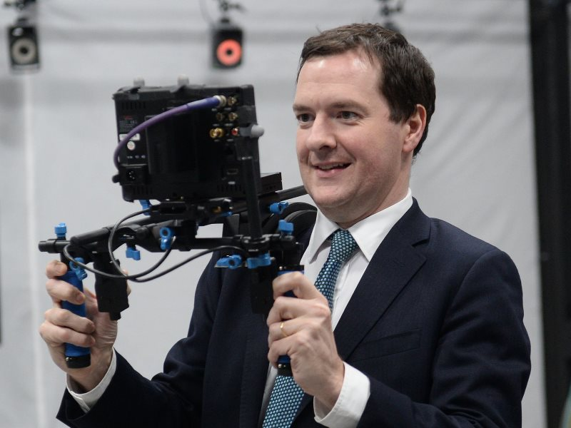 HM Chancellor George Osborne gazing happily at his vision of the future, courtesy of Ealing Studios. Sadly, the device has a fault - and it's actually taking him back to the 1950s. Photo: PA / HM Treasury via Flickr (CC BY-NC-ND).