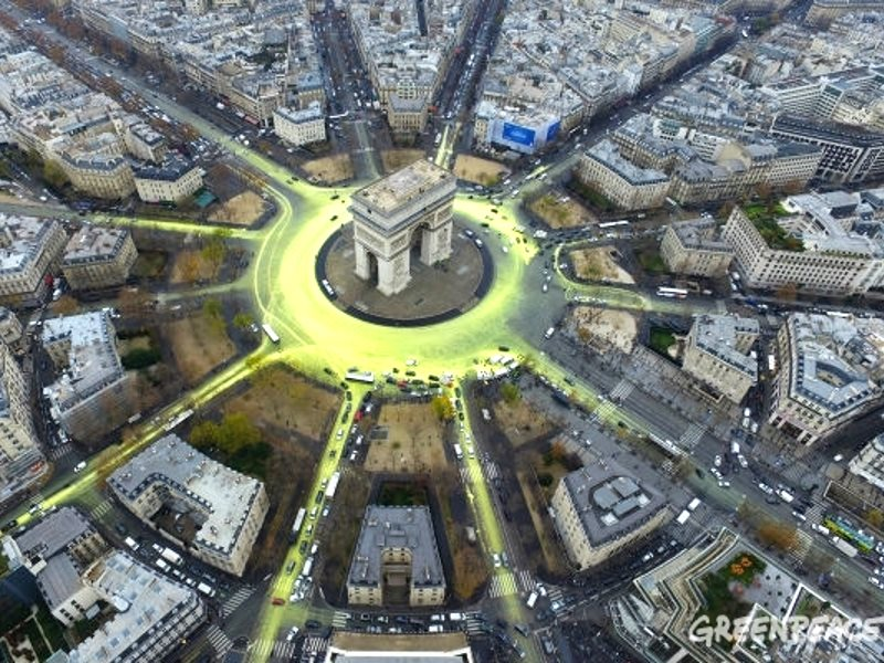 The Arc de Triomphe in Paris, turned into a giant symbol of the Sun after hundreds of bicycles dribbled yellow paint on the Etoile roundabout and surrounding avenues. Photo: Greenpeace.