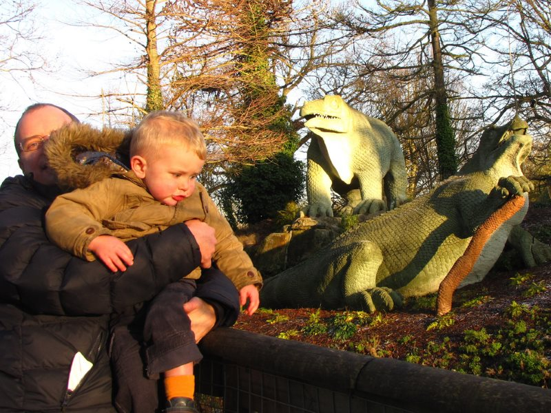 Two individuals of a fearsome species that's inflicting mass extinction on our planet, and (right) a couple of harmless Victorian dinosaurs at Crystal Palace Park, South London. Photo: London looks via Flickr (CC BY).