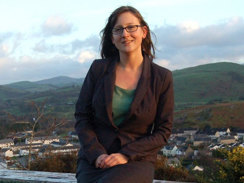 Alice Hooker-Stroud, leader of the Wales Green Party, on a hill overlooking her home town of Machynlleth in West Mid-Wales. Photo: Alex Randall via Flickr (CC BY-NC-ND).